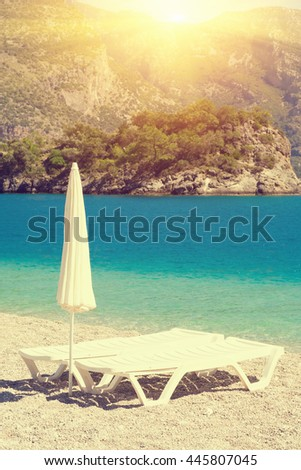 White chaise longues with a closed parasol on the sandy shore of the sea, sunny - stock photo