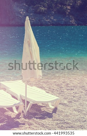 White chaise longues with a closed parasol on the sandy shore of the sea. Toned - stock photo