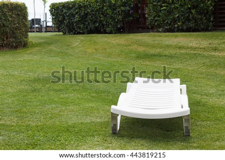 White chaise lounge on the grass lawn