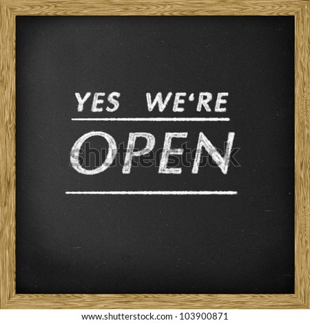 White chalk writing 'yes we're open' on Chalkboard blackboard, Square. - stock photo