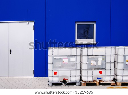 White chemical container in front of a blue industrial building