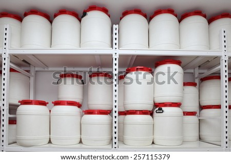 white chemical plastic barrels on shelves in storehouse - stock photo