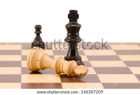 white chess king lie near winner black on chess board isolated on white.  - stock photo