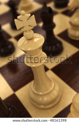White chess king on chess board - very shallow depth of field with focus on the top of the king - stock photo