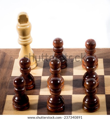 White chess king surrounded of black pawns on a chess board - stock photo