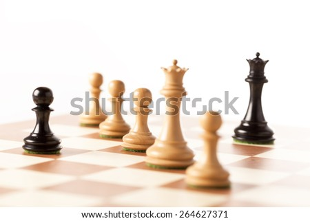 White chess pieces standing on a chessboard with black pawn and queen at both sides - stock photo