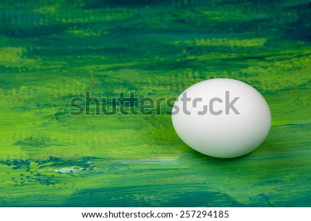 White chicken egg on green painted background. Symbol of life and Easter.