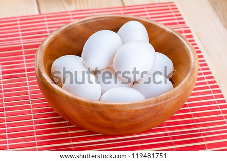 White chicken eggs in wooden bowl on red napkin. - stock photo