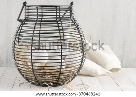 White chicken eggs on straw in black wire basket and linen towel on rustic wooden table. - stock photo