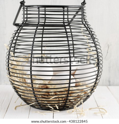 White chicken eggs on straw in black wire basket on rustic wooden table. - stock photo