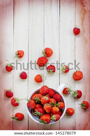 White china bowl filled with succulent juicy fresh ripe red strawberries on wooden table top - stock photo