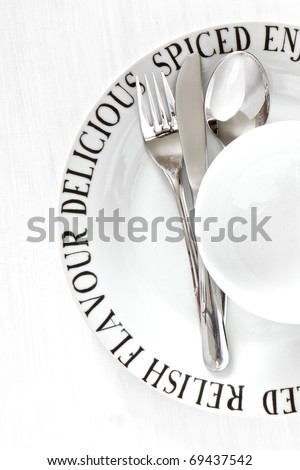 White china plate and bowl with silver utensils on whitewashed wood - stock photo