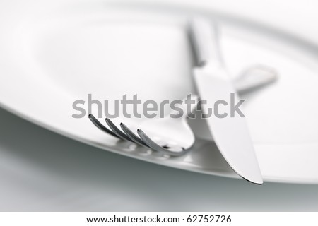 White china plate with crossed silver knife and fork cutlery, shallow deep of field with focus on tip of fork - stock photo