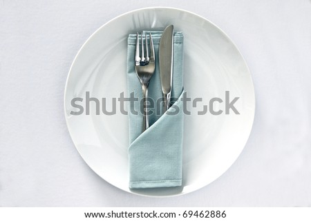 White china plate with serivette and knife and fork isolated on a white background - stock photo
