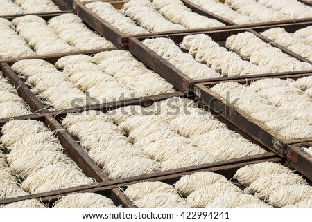 White chinese noodles in wooden trays drying outdoor under the sun