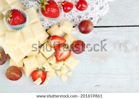 White chocolate bar with fresh berries, on color wooden background - stock photo