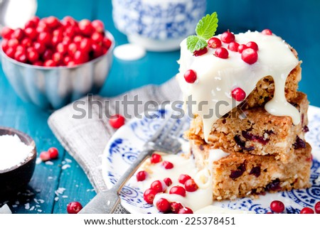 White chocolate cake, blondie, brownie with cranberry and coconut on a white and blue wooden background - stock photo