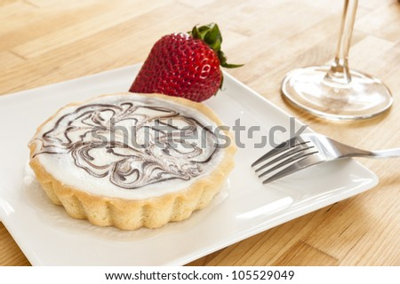 White chocolate cheesecake tart dessert with a strawberry - stock photo