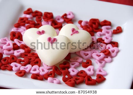White chocolate hearts on a bed of heart sprinkles - stock photo
