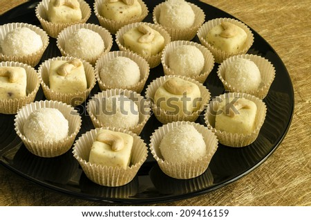 White chocolate homemade truffles with cashew on black plate From series elegant desserts - stock photo