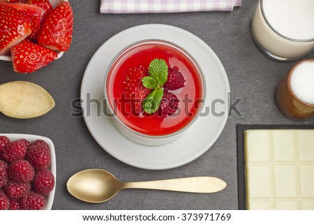 White chocolate panna cotta with raspberries and strawberries on a slate plate with ingredients, a golden spoon and a purple napkin - stock photo