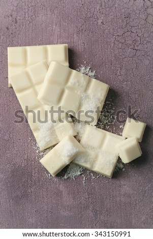 White chocolate pieces and coconut shavings on color wooden background - stock photo