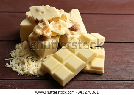White chocolate pieces with nuts on color wooden background - stock photo