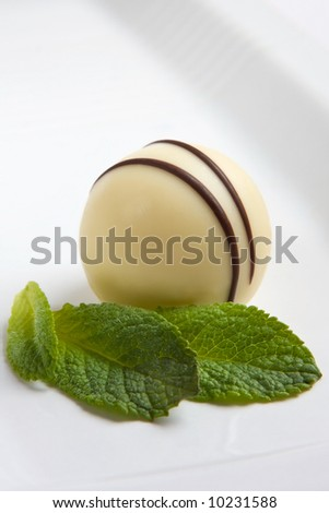 White chocolate truffle and mint leaf - stock photo