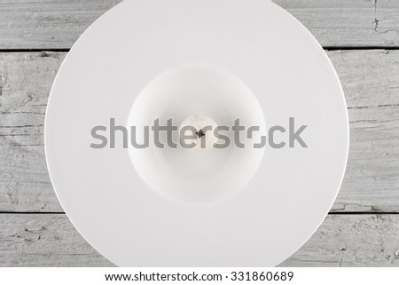 white chocolate truffle on a plate shot on white wooden boards from above