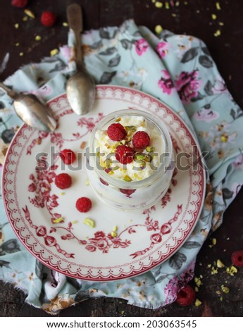White chocolate whipped cream dessert with fresh raspberry and chopped pistachios in a jar, selective focus - stock photo