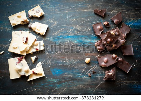 White chocolate with hazelnuts and cranberries and dark chocolate with hazelnuts. Top view. - stock photo