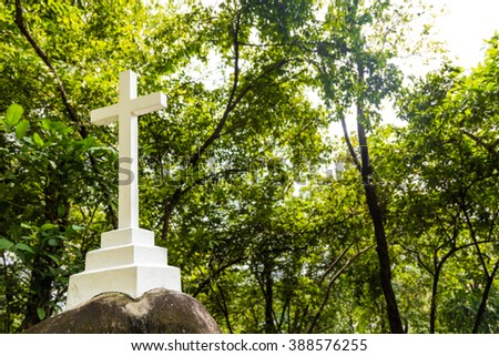 White Christian cross crucifix structure stationed within greenery nature setting - stock photo