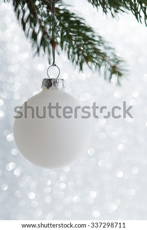 White christmas ball on the xmas tree on glitter bokeh background. Merry christmas card. Winter holidays. Xmas theme. Happy New Year. - stock photo