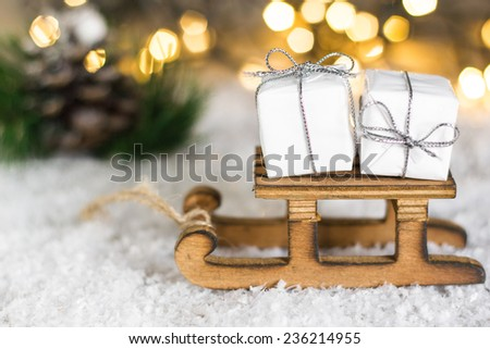 White christmas gift box on a wooden sleigh with christmas lights in the background. - stock photo