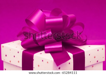 White christmas gift box with purple ribbon on pink background