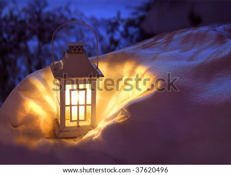 White Christmas lantern in snow, with yellow candle light, on mysterious dark blue background - stock photo