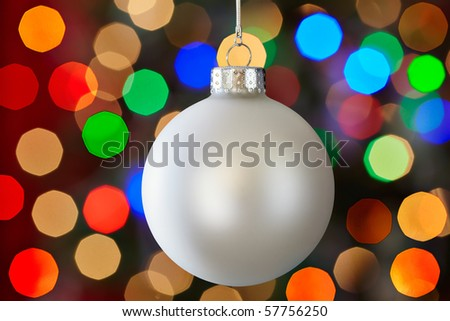 White Christmas Ornament Over Colorful Multicolored Christmas Light Bokeh Background - stock photo