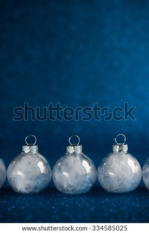 White christmas ornaments on dark blue glitter background with space for text. Merry christmas card. Winter holidays. Xmas theme. Happy New Year. - stock photo