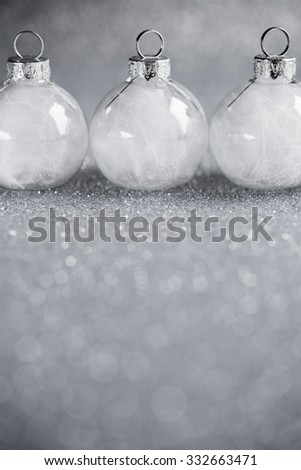 White christmas ornaments on silver glitter background with space for text. Merry christmas card. Winter holidays. Xmas theme. - stock photo