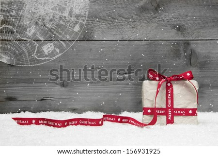 White Christmas present with long ribbon, snow on grey wooden background - stock photo