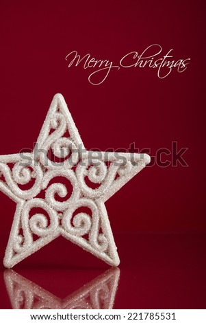 White christmas star on dark red background with space for text. Xmas holiday theme. - stock photo