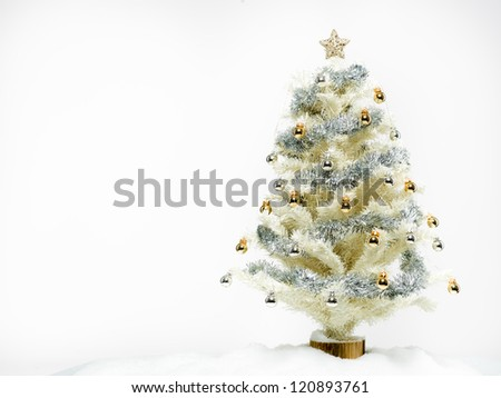 white christmas tree beautifully decorated with shiny golden and silver decorations surrounded with artificial snow isolated on white background - stock photo