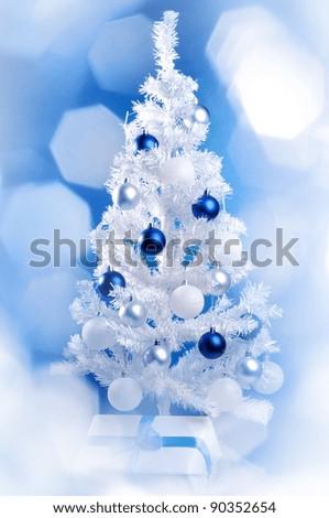 White Christmas tree behind the frozen window - stock photo