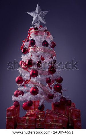 white Christmas tree,big silver star,red decoration, red gift boxes ,grey background  - stock photo