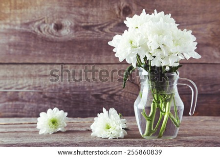 White chrysanthemum flowers in jug on grey wooden background.Toned image - stock photo