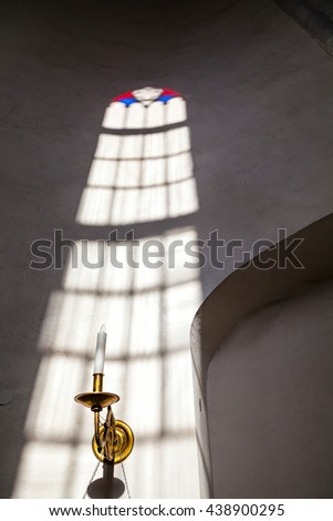 White church wall inside with rays of light going through stained glass window - stock photo
