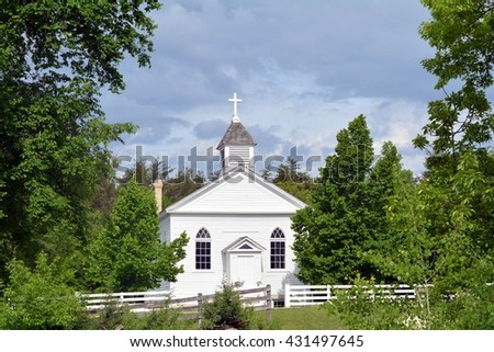 White church with fence and trees