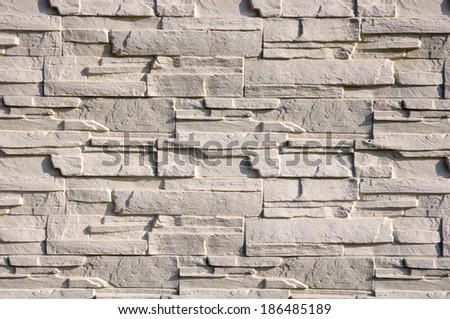 White cladding tiles imitating stones in sunny day  - stock photo