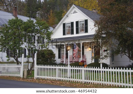 White clapboard house with a white picket fence - stock photo