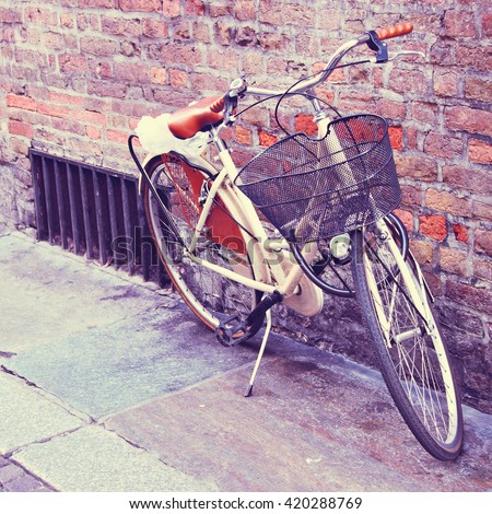 White classic bicycle in the town. Filtered image. - stock photo